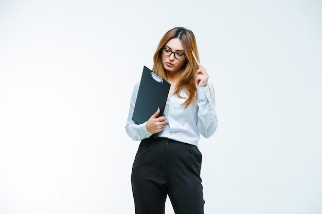 Młoda kobieta trzyma długopis na świątyni podczas myślenia