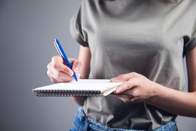 Młoda kobieta trzyma długopis z notatnikiem