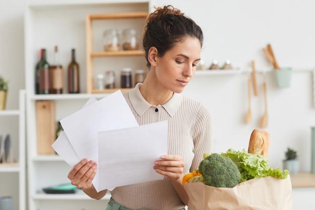 Młoda kobieta trzyma dokumenty i sprawdza produkty w papierowej torbie, stojąc w kuchni