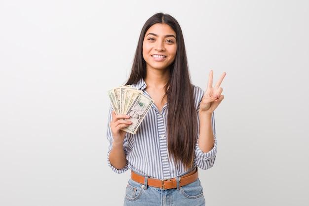 Młoda kobieta trzyma dolary pokazuje numer dwa z palcami.