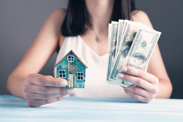 Młoda kobieta trzyma dom i pieniądze