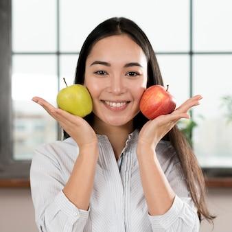 Młoda kobieta trzyma dwa zielonego i czerwonego jabłka