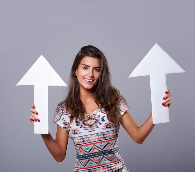 Młoda kobieta trzyma dwa znaki strzałki