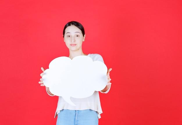 Młoda kobieta trzyma dymek w kształcie chmury