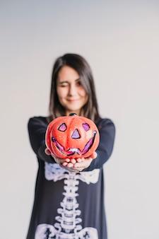 Młoda kobieta trzyma dyni i robi mrugnięcie twarzy. ubrany w czarno-biały kostium szkieletu. koncepcja halloween. wewnątrz. styl życia