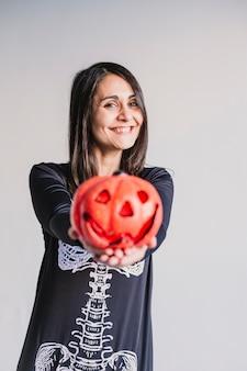 Młoda kobieta trzyma dyni i uśmiecha się. ubrany w czarno-biały kostium szkieletu. koncepcja halloween. wewnątrz. styl życia