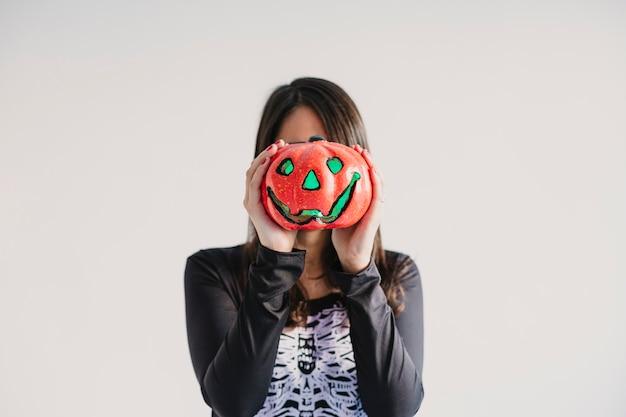 Młoda kobieta trzyma dyni zakrywa jej twarz. ubrany w czarno-biały kostium szkieletu. koncepcja halloween. wewnątrz. styl życia