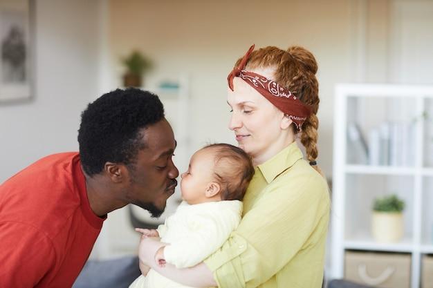 Młoda kobieta trzyma dziecko na rękach, podczas gdy afrykański mężczyzna ją całuje, są w domu