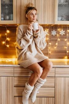Młoda kobieta trzyma filiżankę herbaty w przytulnych ubraniach