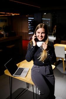 Młoda kobieta trzyma filiżankę kawy i za pomocą laptopa rozmawia przez telefon. kobieta pracuje w domu. praca w domu