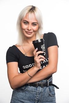 Młoda kobieta trzyma filiżankę kawy na białej ścianie z rękami skrzyżowanymi.