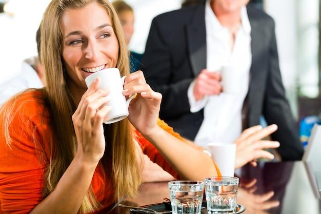 Młoda kobieta trzyma filiżankę kawy w ręku