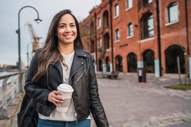 Młoda kobieta trzyma filiżankę kawy.