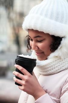 Młoda kobieta trzyma filiżankę wielokrotnego użytku w zimie