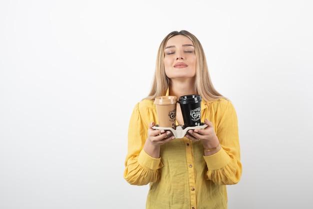 Młoda kobieta trzyma filiżanki kawy i wącha je.