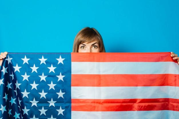 Młoda kobieta trzyma flagę usa przed nią na niebieskim tle.
