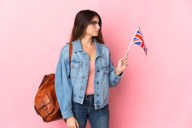 Młoda kobieta trzyma flagę zjednoczonego królestwa na białym tle na różowo, patrząc z boku