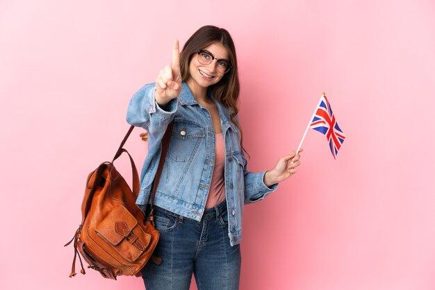 Młoda kobieta trzyma flagę zjednoczonego królestwa na białym tle na różowo pokazując i podnosząc palec