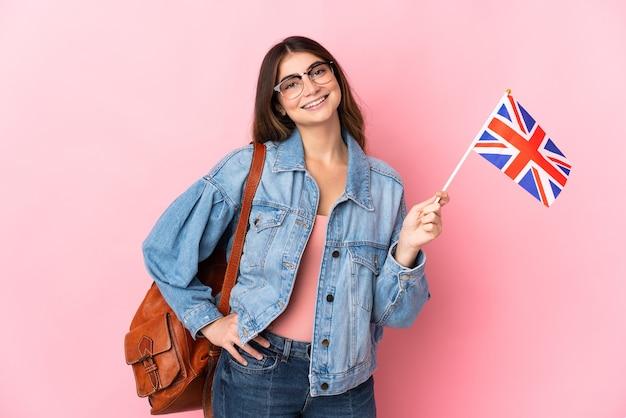 Młoda kobieta trzyma flagę zjednoczonego królestwa na białym tle na różowo, pozowanie z rękami na biodrze i uśmiechnięty