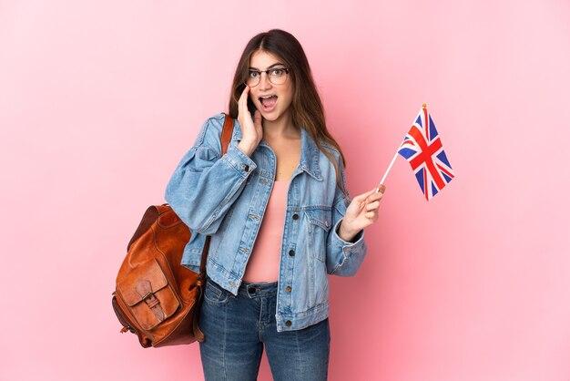 Młoda kobieta trzyma flagę zjednoczonego królestwa na białym tle na różowo z zaskoczeniem i zszokowany wyraz twarzy