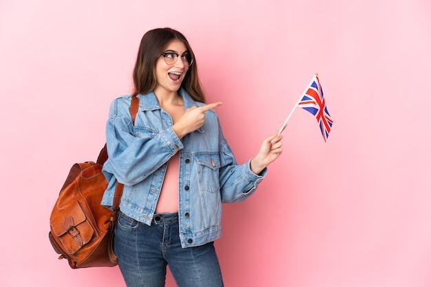 Młoda kobieta trzyma flagę zjednoczonego królestwa na białym tle na różowym palcem wskazującym z boku i przedstawia produkt