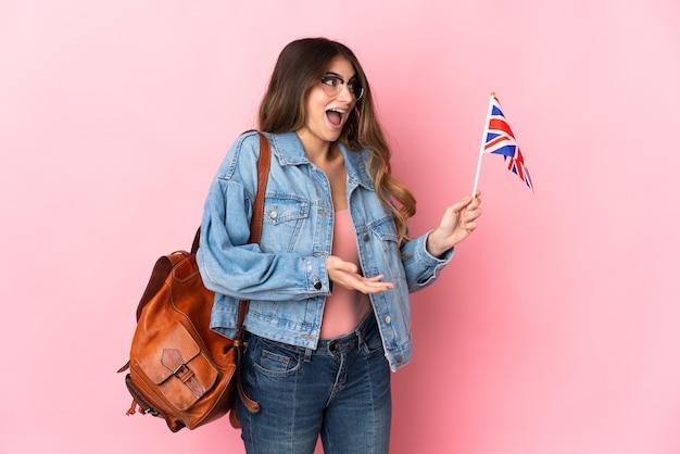 Młoda kobieta trzyma flagę zjednoczonego królestwa samodzielnie na różowo z wyrazem zaskoczenia, patrząc z boku