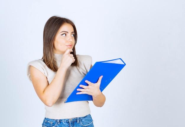 Młoda kobieta trzyma folder i myśli.