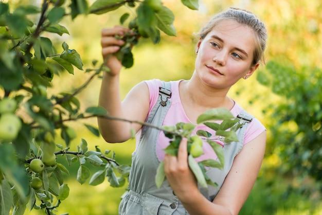 Młoda kobieta trzyma gałęzie drzew