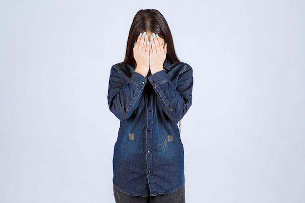 Młoda kobieta trzyma głowę, gdy jest zmęczona lub ma ból głowy