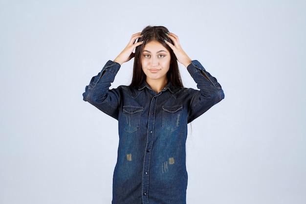 Młoda kobieta trzyma głowę i myśli