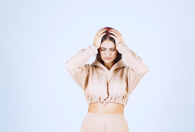 Młoda kobieta trzyma głowę, ponieważ ma ból głowy
