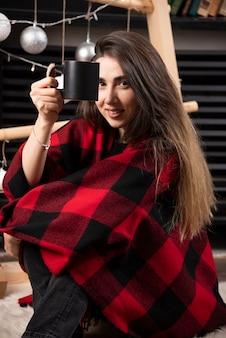 Młoda kobieta trzyma gorącą filiżankę w kratkę w kratę.