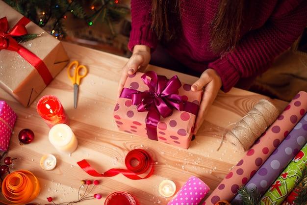 Młoda kobieta trzyma gotowy owinięty prezent nad stołem z różnymi dekoracjami wokół