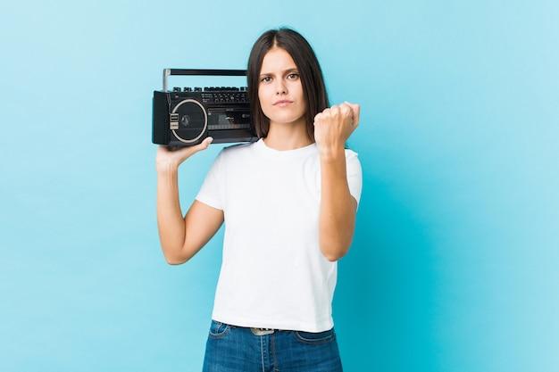 Młoda kobieta trzyma guetto blaster pokazuje pięść