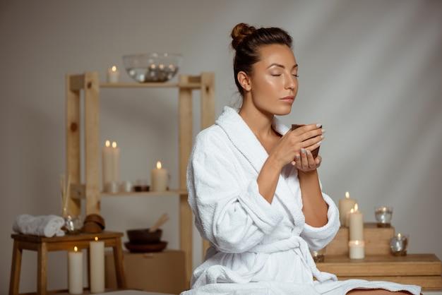 Młoda kobieta trzyma herbacianą filiżankę relaksuje w zdroju salonie.