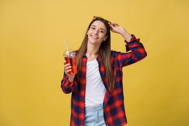 Młoda kobieta trzyma i pije napój zimny napój w ubranie. ładna dziewczyna uśmiechający się szczęśliwy śmiejąc się patrząc na kamery.
