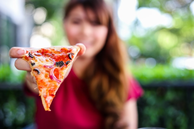 Młoda kobieta trzyma i pokazuje pyszną pizzę.