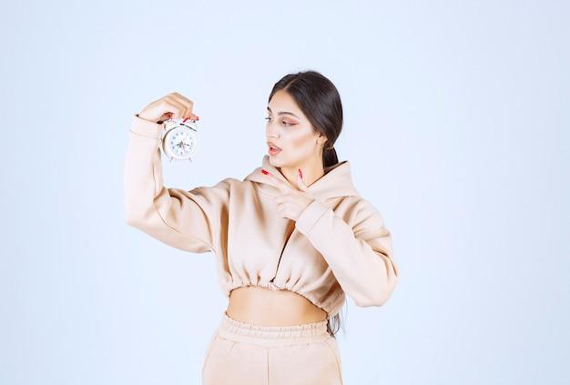 Młoda kobieta trzyma i promuje nowy model budzika