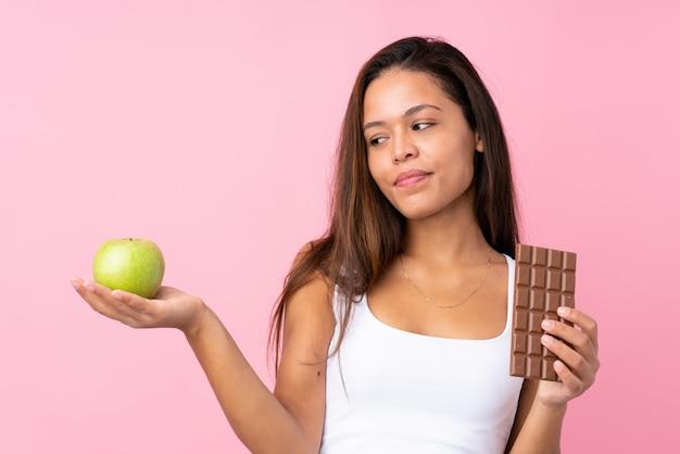 Młoda kobieta trzyma jabłka i czekolady nad odosobnioną ścianą