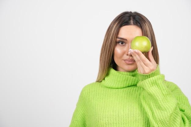Młoda kobieta trzyma jabłko w zielonej koszulce.