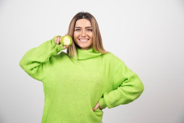 Młoda kobieta trzyma jabłko w zielonej koszulce