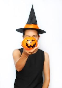 Młoda kobieta trzyma jack bani na białym tle w czarownicach.