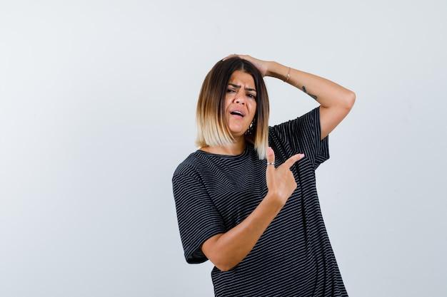 Młoda kobieta trzyma jedną rękę na głowie, wskazując w prawo z palcem wskazującym w czarnej sukience i patrząc zmartwiony, widok z przodu.