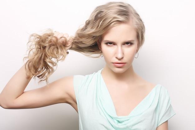 Młoda kobieta trzyma jej długie kręcone zdrowe włosy