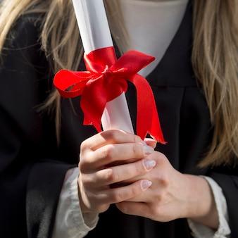 Młoda kobieta trzyma jej dyplomu zakończenie