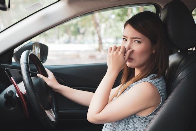Młoda kobieta trzyma jej nos z powodu złego zapachu w samochodzie