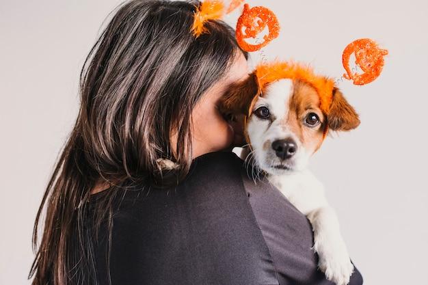 Młoda kobieta trzyma jej ślicznego małego psa nad dopasowywanie dyniowych diademami. koncepcja halloween. wewnątrz