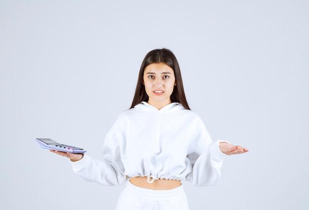 Młoda kobieta trzyma kalkulator na biało szarym tle.