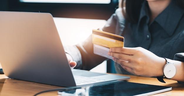 Młoda kobieta trzyma kartę kredytową i przy użyciu komputera przenośnego. koncepcja zakupów online.