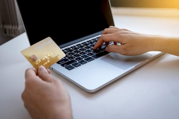 Młoda kobieta trzyma kartę kredytową i wpisując na komputerze przenośnym